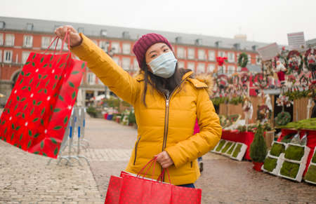 Asian girl enjoying Christmas shopping  - young happy and beautiful Chinese woman with mask holding red shopping bag buying presents on xmas street market