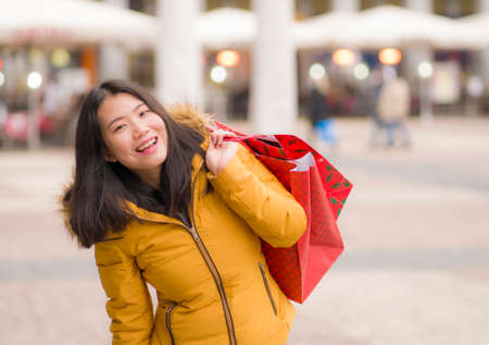 Asian girl enjoying Christmas shopping - young happy and beautiful Chinese woman holding red shopping bag buying presents at street xmas market smiling cheerful