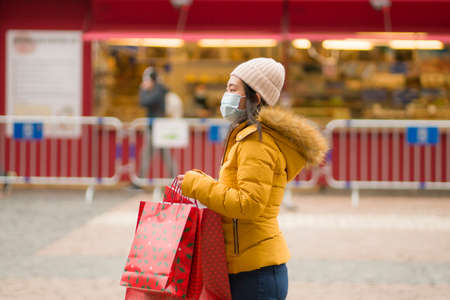 Asian girl enjoying Christmas shopping   - young happy and beautiful Japanese woman with mask holding red shopping bag buying presents on xmas street market 스톡 콘텐츠