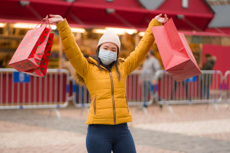 Asian girl enjoying Christmas shoppingv - young happy and beautiful Chinese woman with mask holding red shopping bag buying presents on xmas street market