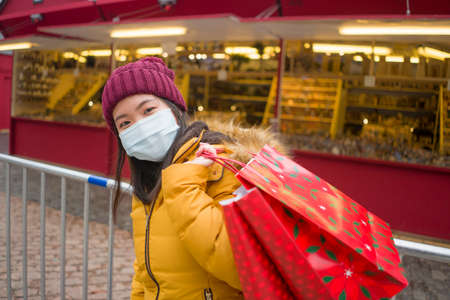 Asian girl enjoying Christmas shopping    young happy and beautiful Korean woman with mask holding red shopping bag buying presents on xmas street market
