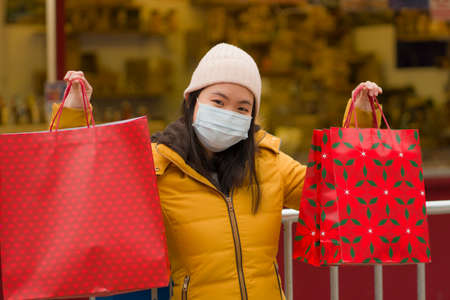 Asian girl enjoying Christmas shopping d  - young happy and beautiful Japanese woman with mask holding red shopping bag buying presents on xmas street market