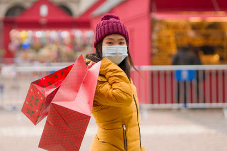 Asian girl enjoying Christmas shopping    - young happy and beautiful Japanese woman with mask holding red shopping bag buying presents on xmas street market
