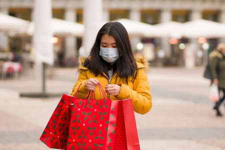 Asian girl enjoying Christmas shopping during  - young happy and beautiful Korean woman with mask holding red shopping bag buying presents on xmas street market