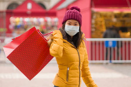 Asian girl enjoying Christmas shopping during  - young happy and beautiful Chinese woman with mask holding red shopping bag buying presents on xmas street market