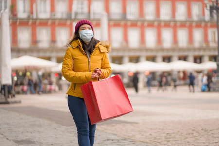 Asian girl enjoying Christmas shopping during  - young happy and beautiful Chinese woman with mask holding red shopping bag buying presents on xmas street market Imagens - 162165312