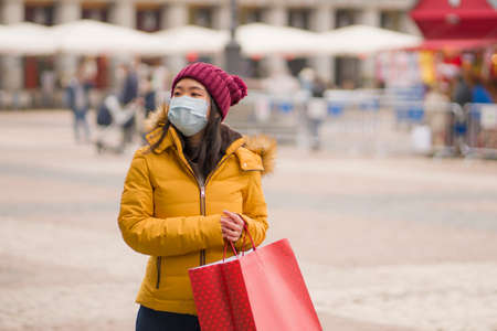 Asian girl enjoying Christmas shopping during  - young happy and beautiful Chinese woman with mask holding red shopping bag buying presents on xmas street market Imagens - 162165316