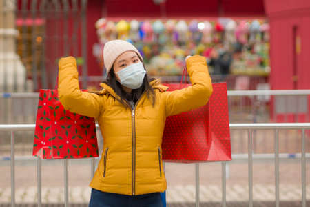 Asian girl enjoying Christmas shopping during covid19 - young happy and beautiful Chinese woman with mask holding red shopping bag buying presents on xmas street market