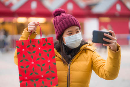 Asian girl enjoying Christmas shopping during  - young happy and beautiful Japanese woman holding red shopping bag taking selfie with presents on xmas street market 스톡 콘텐츠