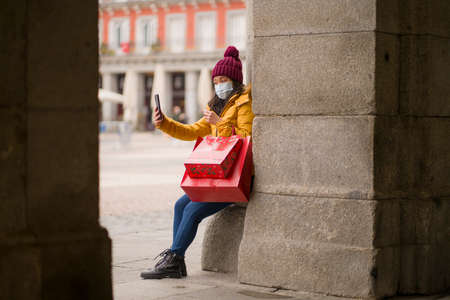 Asian girl enjoying Christmas shopping during  - young happy and beautiful Korean woman holding red shopping bag taking selfie with presents on xmas street market 스톡 콘텐츠