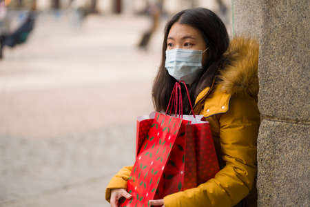 Asian girl enjoying Christmas shopping during covid19 - young happy and beautiful Korean woman with mask holding red shopping bag buying presents on xmas street market 版權商用圖片