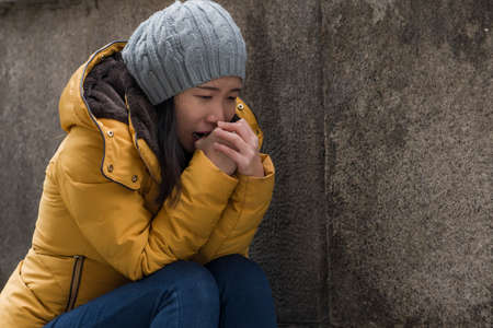 dramatic lifestyle portrait of young attractive sad and depressed Korean woman in winter hat sitting outdoors on street corner staircase suffering depression problem crying