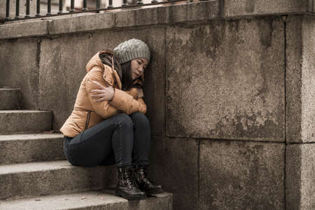 dramatic lifestyle portrait of young attractive sad and depressed Chinese woman in winter hat sitting outdoors on street corner staircase suffering depression problem crying helpless