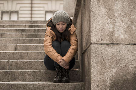 dramatic lifestyle portrait of young attractive sad and depressed Japanese woman in winter hat sitting outdoors on street corner staircase suffering depression problem crying helpless