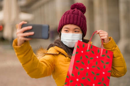 Asian girl enjoying Christmas shopping during covid19 - young happy and beautiful Chinese woman holding red shopping bag taking selfie with presents on xmas street market