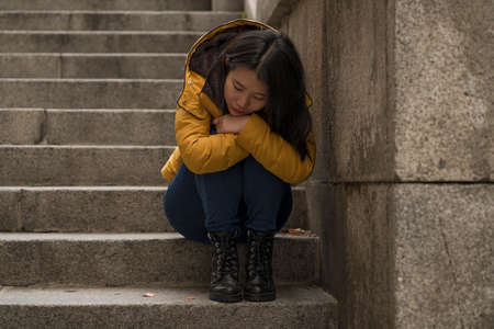 dramatic lifestyle portrait of young attractive sad and depressed Japanese woman in winter jacket sitting outdoors on street corner staircase suffering depression problem feeling helpless 版權商用圖片