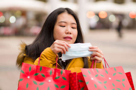 Asian girl enjoying Christmas shopping during covid19 - young happy and beautiful Korean woman putting face mask holding red shopping bag buying presents on xmas street market 版權商用圖片