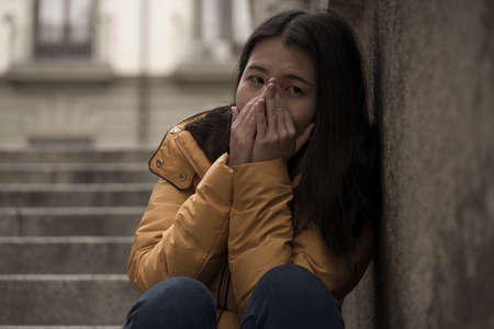 young attractive sad and depressed Chinese woman in winter jacket sitting outdoors on street corner staircase suffering depression problem feeling helpless