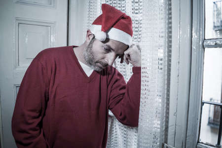 dramatic lifestyle portrait of sad and depressed man in Santa Claus hat feeling lonely home alone by Christmas holiday thoughtful at the window in unhappy xmas concept