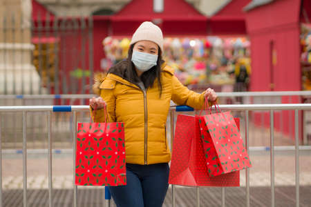 Asian girl enjoying Christmas shopping during covid19 - young happy and beautiful Japanese woman with mask holding red shopping bag buying presents on xmas street market