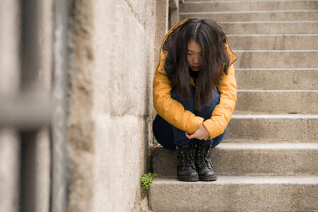 dramatic lifestyle portrait of young attractive sad and depressed Korean woman in winter jacket sitting outdoors on street corner staircase suffering depression problem feeling helpless
