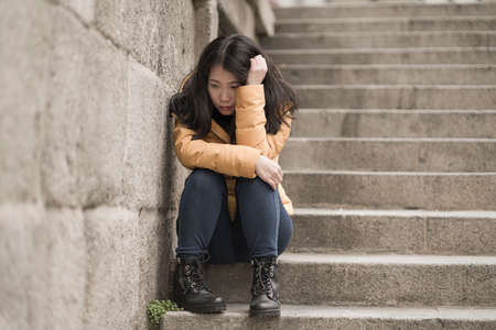 dramatic lifestyle portrait of young attractive sad and depressed Japanese woman in winter jacket sitting outdoors on street corner staircase suffering depression problem feeling helpless