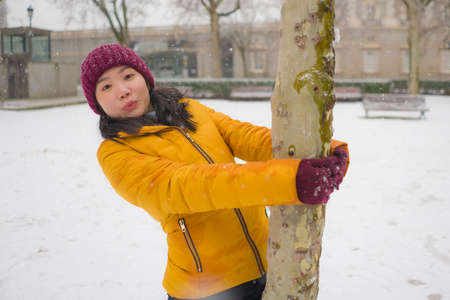 young happy and attractive Asian Chinese woman in Winter jacket and beanie enjoying snowfall at city park playing cheerful surrounded by snow during Christmas holidays Standard-Bild