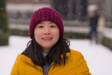 young happy and attractive Asian Korean woman in Winter jacket and beanie enjoying snowfall at city park playing cheerful surrounded by snow during Christmas holidays