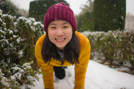 young happy and attractive Asian Japanese woman in Winter jacket and beanie enjoying snowfall at city park playing cheerful surrounded by snow during Christmas holidays