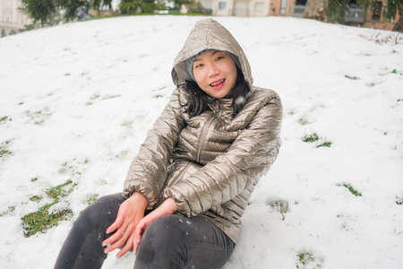 lifestyle portrait of  young happy and attractive Asian Japanese woman in winter hat and mask at beautiful city park playing with snow cheerful enjoying cold Christmas holidays