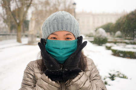 snowfall in covid19 time - young happy and attractive Asian Chinese woman in winter hat and mask at beautiful city park playing with snow cheerful enjoying cold Christmas holidays 免版税图像