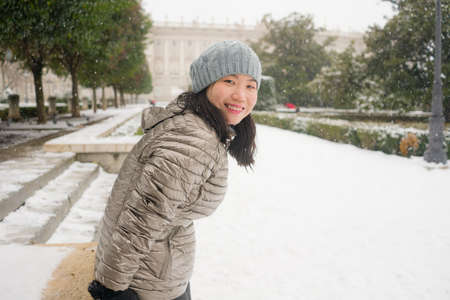 lifestyle portrait of  young happy and attractive Asian Chinese woman in winter hat and mask at beautiful city park playing with snow cheerful enjoying cold Christmas holidays 免版税图像
