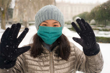 snowfall in covid19 time - young happy and attractive Asian Korean woman in winter hat and mask at beautiful city park playing with snow cheerful enjoying cold Christmas holidays