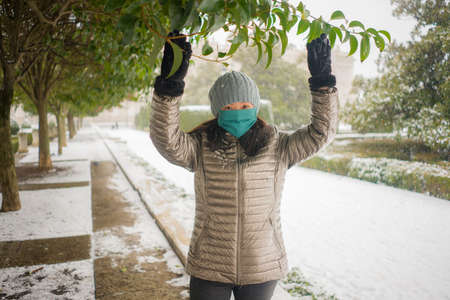 snowfall in covid19 time - young happy and attractive Asian Japanese woman in winter hat and mask at beautiful city park playing with snow cheerful enjoying cold Christmas holidays