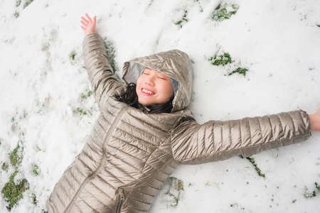 lifestyle portrait of  young happy and attractive Asian Korean woman in winter hat and mask at beautiful city park playing with snow cheerful enjoying cold Christmas holidays