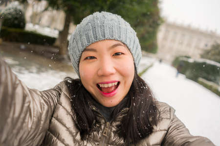 winter lifestyle portrait of young happy and beautiful Asian Korean woman taking selfie picture with mobile phone enjoying snow at city park during Christmas holidays travel 免版税图像