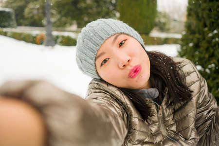 winter lifestyle portrait of young happy and beautiful Asian Japanese woman taking selfie picture with mobile phone enjoying snow at city park during Christmas holidays travel