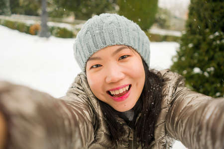 winter lifestyle portrait of young happy and beautiful Asian Chinese woman taking selfie picture with mobile phone enjoying snow at city park during Christmas holidays travel