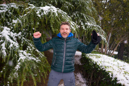 urban winter lifestyle portrait of young happy and attractive tourist man walking cheerful in city park during Christmas snowfall enjoying and playing with snow