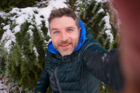 young happy and attractive tourist man taking selfie portrait with mobile phone cheerful in city park during Christmas snowfall enjoying and playing with snow