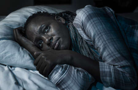 dramatic home portrait of young sick and depressed black African American girl sitting on bed  upset and sleepless at night feeling overwhelmed suffering depression and anxiety problem