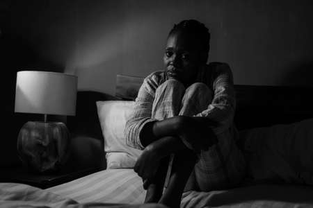 dramatic home portrait of young sick and depressed black afro American girl sitting on bed  upset and sleepless at night feeling overwhelmed suffering depression and anxiety problem 스톡 콘텐츠