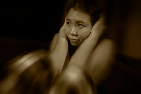 Asian woman suffering depression - dramatic artistic portrait of young beautiful sad and depressed Korean girl in pain helpless on couch at home in the dark
