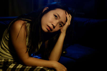 Asian woman suffering depression - dramatic artistic portrait of young beautiful sad and depressed Chinese girl in pain helpless on couch at home in the dark 스톡 콘텐츠