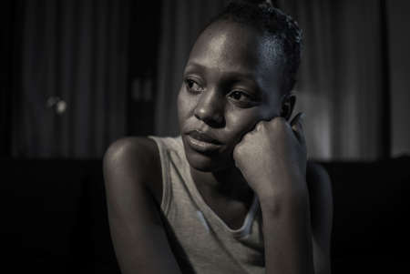 teen African American girl at night suffering depression - dramatic artistic portrait of young attractive sad and depressed black woman worried and upset alone in the dark Imagens - 163466698