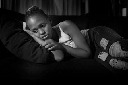 teen African American girl at night suffering depression - dramatic artistic portrait of young attractive sad and depressed black woman worried and upset alone in the dark