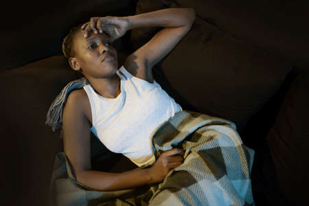 teen afro American girl at night suffering depression - dramatic artistic portrait of young attractive sad and depressed black woman worried and upset alone in the dark 스톡 콘텐츠