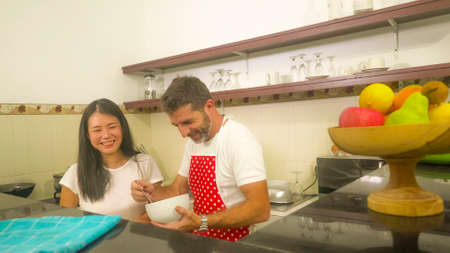 sweet couple cooking together - young beautiful and happy mixed ethnicity couple at home kitchen with wife in red apron with husband hugging her in love and domestic lifestyle concept