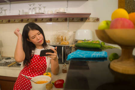 Asian girl confused following online recipe - young sweet and beautiful Korean home cook woman in red apron reading healthy recipe in mobile phone having trouble while cooking