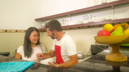 sweet married couple cooking together - young beautiful and happy mixed ethnicity couple at home kitchen with wife in red apron with husband showing love and complicity